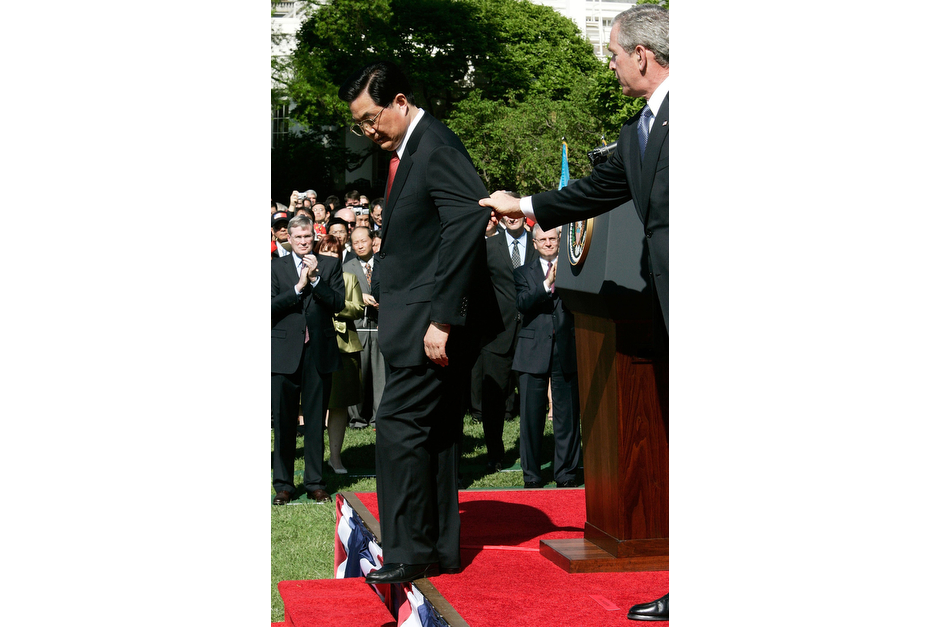 "U.S. President George W. Bush attempts to prevent Chinese President Hu Jintao from stepping off the stage during an arrival ceremony at the South Lawn of the White House, April 20, 2006. Hu was on his first official visit to the United States since taking office in 2002. At the same ceremony, a woman in the press box unfurled a banner of the banned spiritual group Falun Gong and shouted at President Bush, ""Stop this visit."" Later, the White House announcer mistakenly told the crowd they would now hear the national anthem of ""The Republic of China,"" the official name for Taiwan. (Photo by Alex Wong/Getty Images)"
