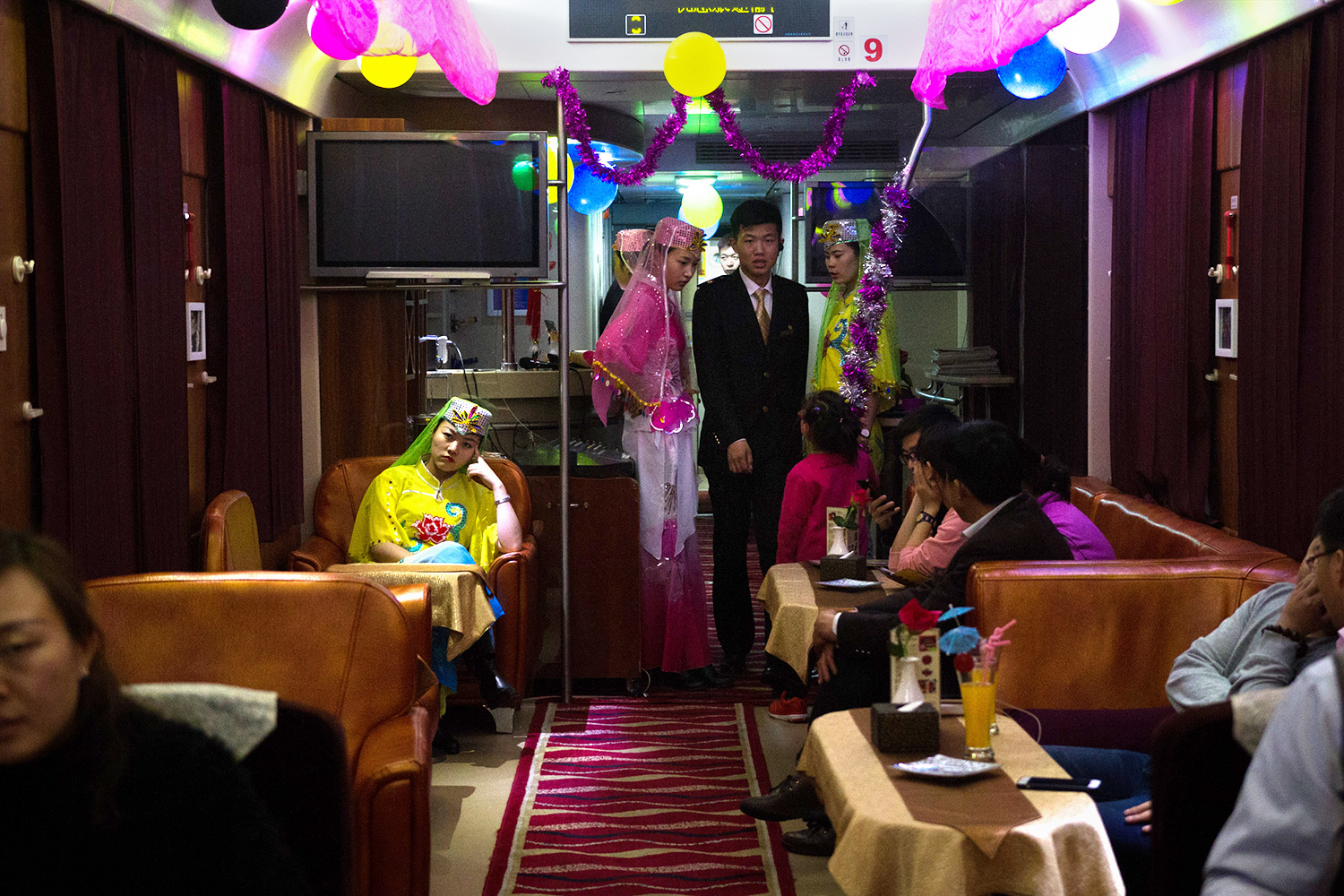 Railway staff dressed in traditional Hui-style outfits wait to perform a dance for the passengers in the dining car of a train bound for the autonomous region of Ningxia.