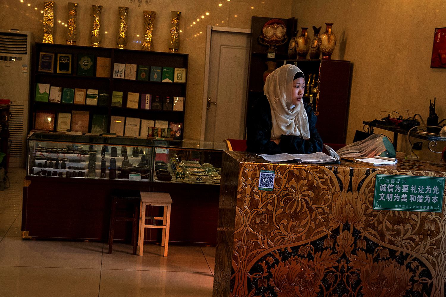 A receptionist inside the Aisha Palace waits to greet visitors. The palace serves as a temporary museum until construction of the main museum is complete.