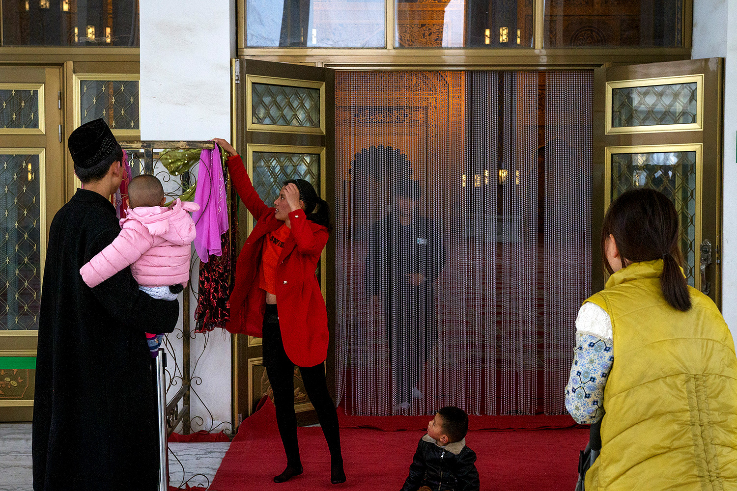A visitor picks out a headscarf to wear before entering the Golden Palace.