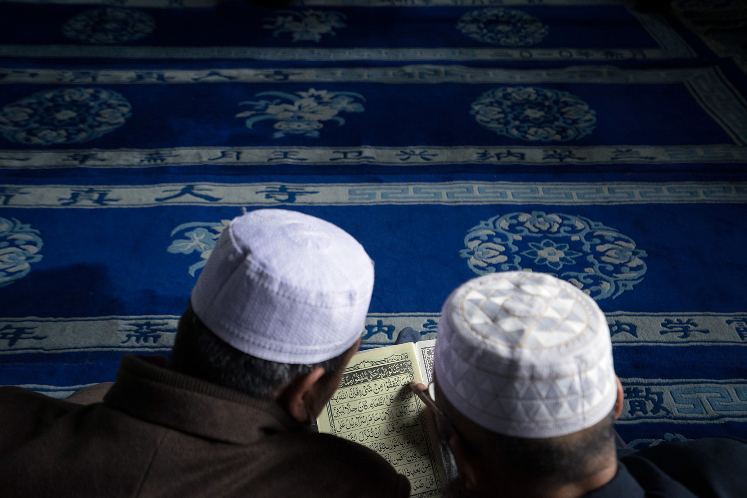 Men share a Quran while sitting on the floor in the main prayer hall of the Najiahu Mosque.
