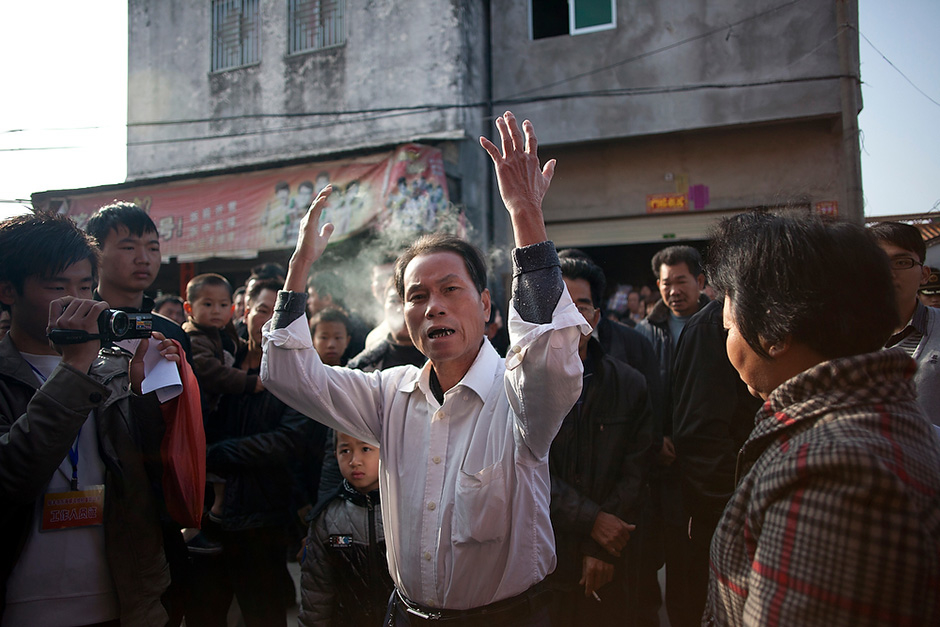 A Wukan villager expresses his exasperation at paramilitary police who turned a foreign journalist away from the polling center during the first of three rounds of village elections.