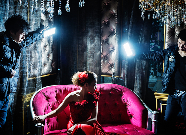 In a different outfit, Tong poses in a solo shot under dramatic lighting cast on her by human light stands at Princess Studio. The studio is not Shanghai's largest, but it is known throughout the city for its creative lighting and the time it puts into making a perfect portrait with each couple.