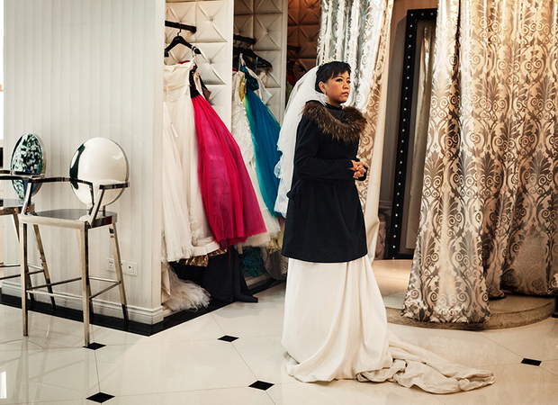 A portrait studio customer waits in a wedding dress for her session to begin at the Dream Castle photo studio.