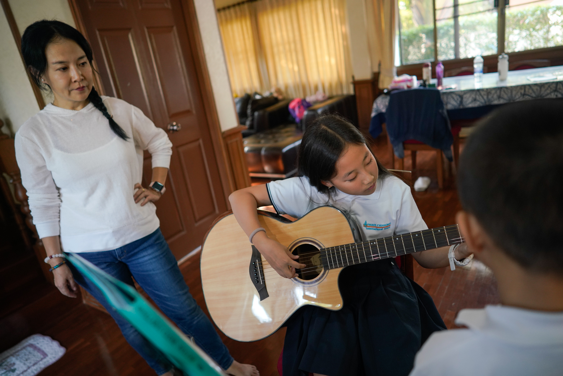 Wang Yixuan watches her eldest daughter, Nina, practice guitar at home, January 22, 2019.