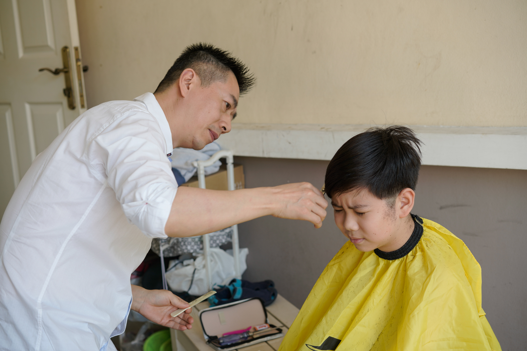 Zou Yanhu's father, Zou Peng, gives him a haircut, January 19, 2019. Zou teaches product design at a university in Chengdu and visits the family in Chiang Mai whenever he has a vacation.
