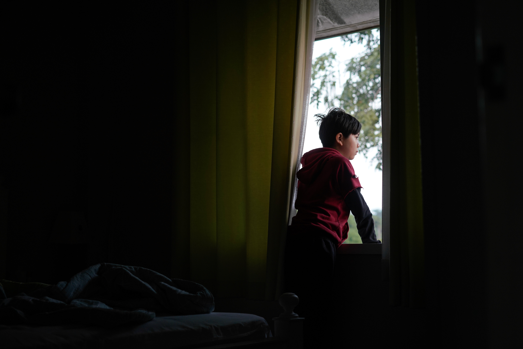 Before heading to school in the morning, Zou Yanhu listens to birds chirping outside his window, something he says he couldn't experience back home in Chengdu, January 18, 2019.