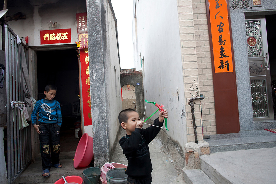 Often described as a relatively wealthy coastal Chinese village, Wukan is nevertheless divided by a visible income gap. Plush new villas stand alongside single-room homes that are crumbling and without running water. Huang Binbin, 6, pulls back on the string of a toy bow and arrow with his brother Pengpeng, 10, nearby. They live in a nine-square-meter home, at left, which they share with their parents and sister.