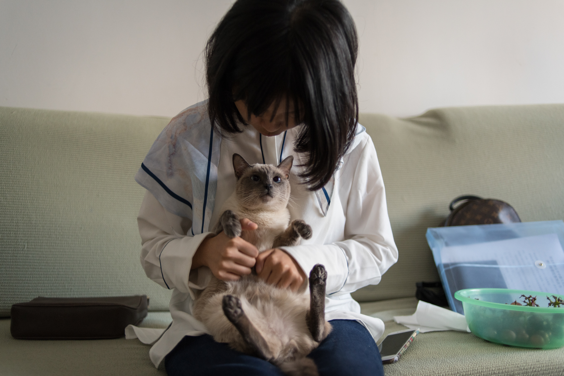 "Zhou with her cat, October 9. Zhou says she used to ask for love from her boyfriend, her family, and her friends, but in her relationships with other victims, she has gradually learned how to give love. ""For example, when you comfort someone, even though she may only feel relieved for five minutes and then fall back to sadness the next day, that five minutes is still meaningful."""