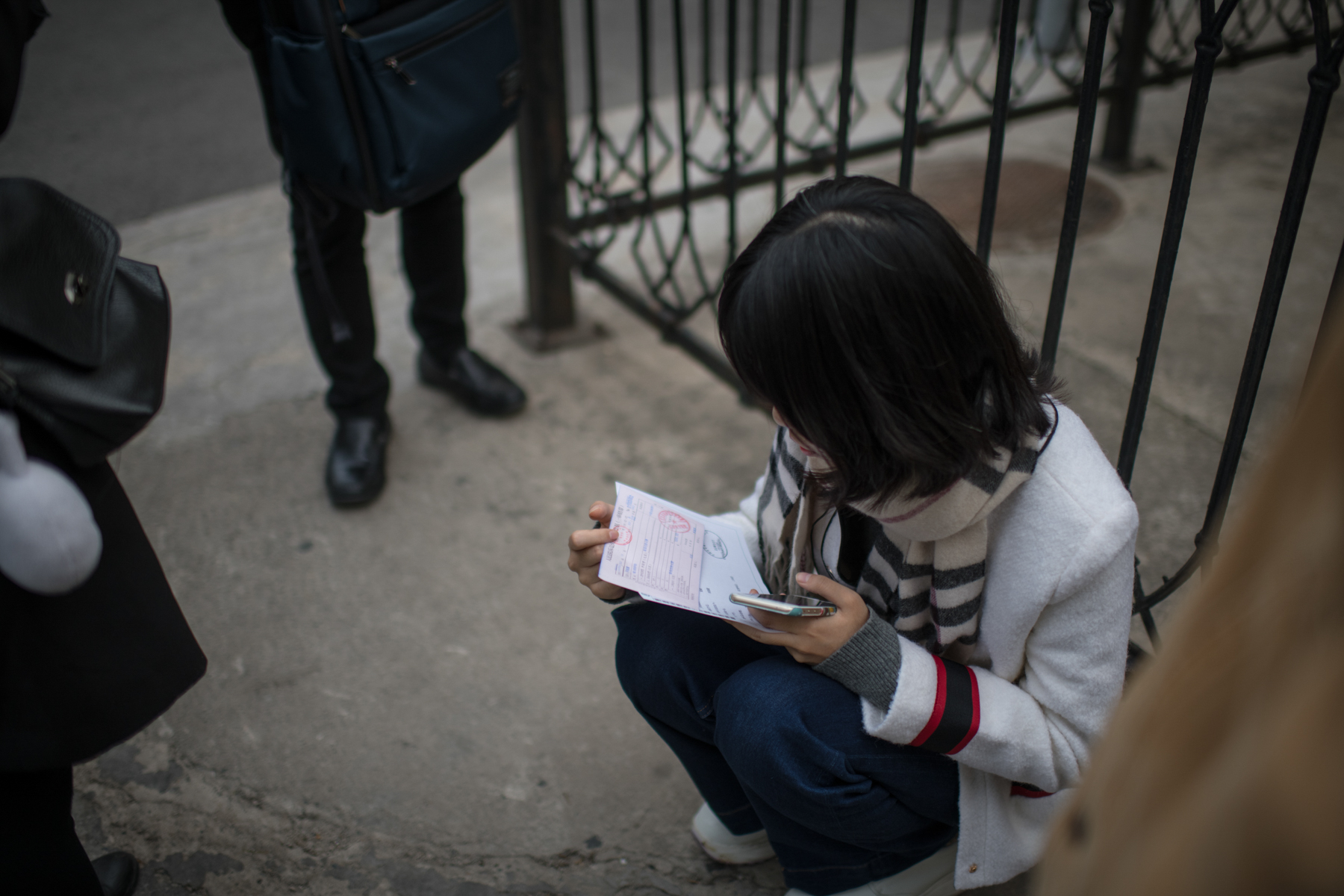 Outside the court, Zhou inspects a certification that her suit against Zhu has been accepted by the court, October 22. Providing evidence for her allegation of sexual harassment, as it is in many such cases, will be extremely difficult.